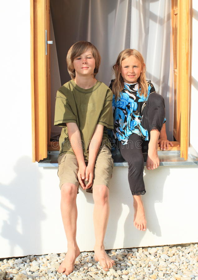 Girl and boy sitting on the window. Smiling barefoot girl in blue - white - black t-shirt and boy in green t-shirt and shorts sitting on opened wooden window stock photography