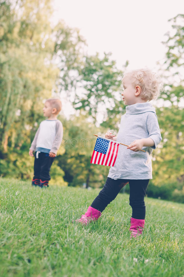 Girl and boy smiling laughing holding hands and waving American flag, outside in park stock image