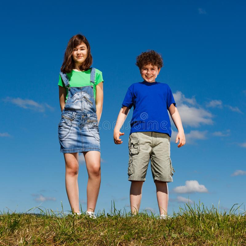 Girl and boy standing outdoor. Smiling stock photography