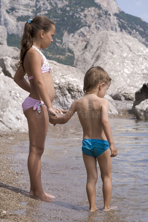 Girl and boy stands in water
