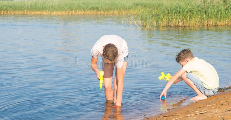 A girl and a boy take water from a lake into water guns in order to play them, against the backdrop of the landscape royalty free stock images