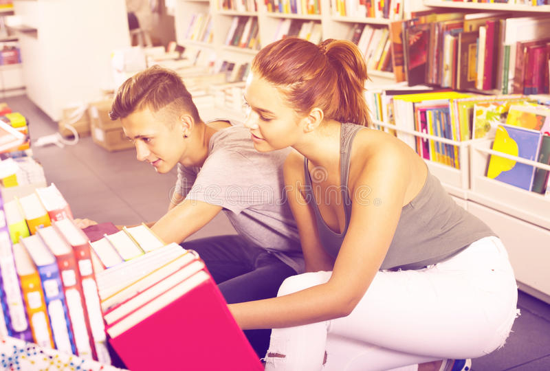Girl and boy teenagers in book store royalty free stock photos