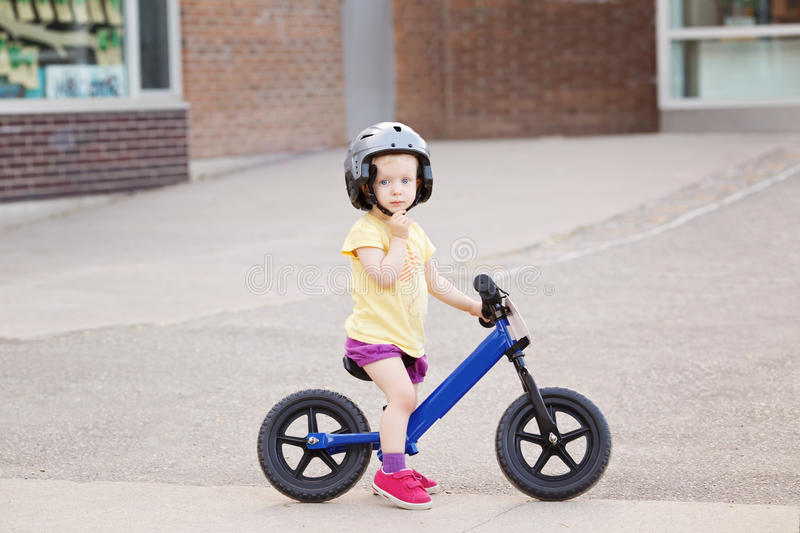 Girl boy toddler riding a balance bike bicycle in helmet on the road stock photography