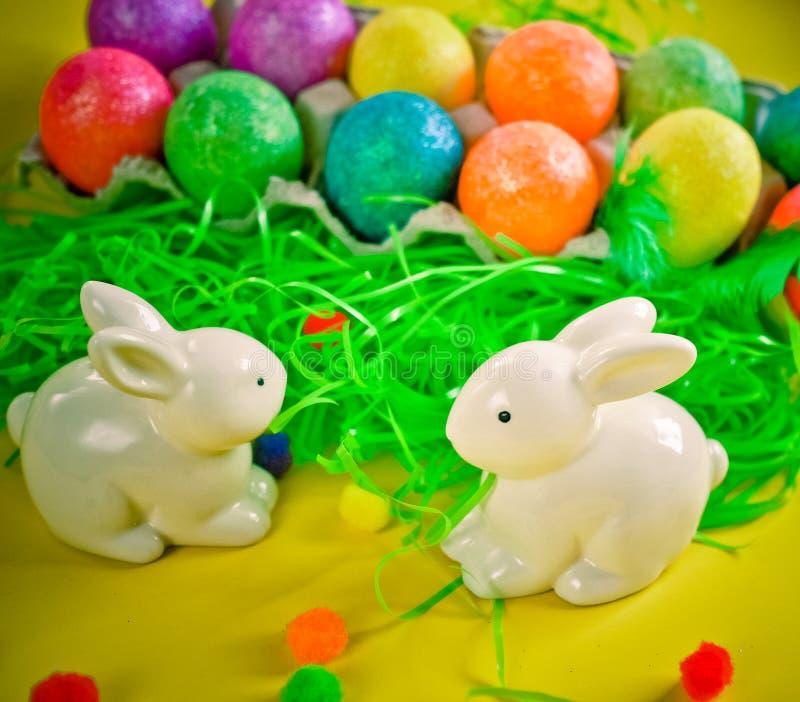 Two white porctlain rabbits near colorful bright eggs stock image