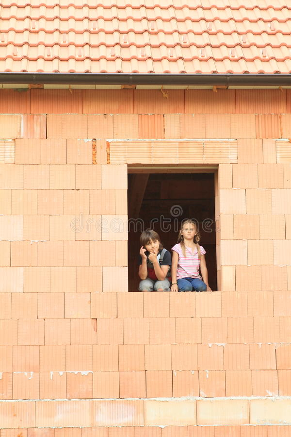 Girl and boy in the window royalty free stock photo