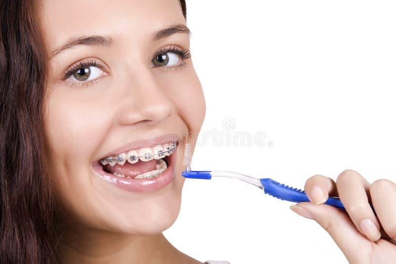 Girl with braces brushing her teeth