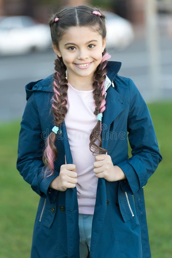 Girl with braided hair style with pink kanekalon. Add bright detail. Little girl with cute braids wear dark coat nature stock photo