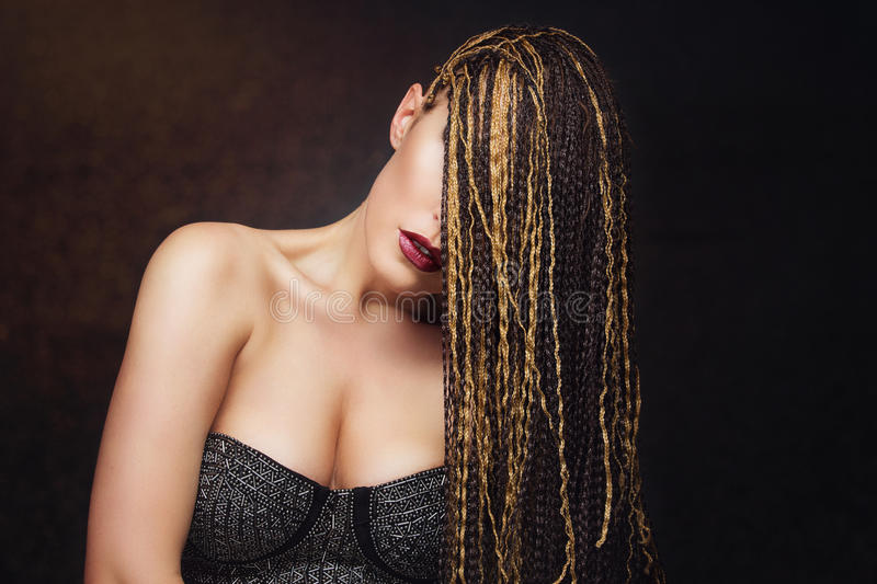 Girl with braids. Closeup portrait of beautiful caucasian young woman with many african braids stock photography