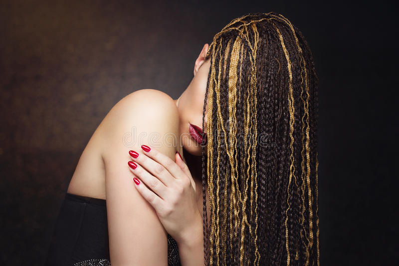 Girl with braids. Closeup portrait of beautiful caucasian young woman with many african braids royalty free stock image