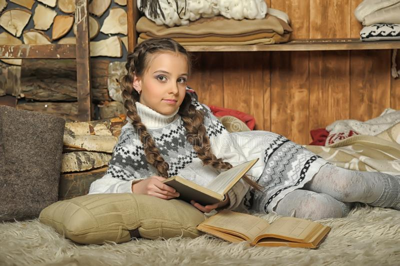 Girl with braids in a sweater lies on a plaid royalty free stock photos