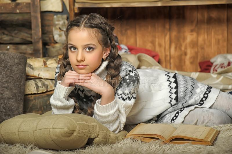 Girl with braids in a sweater lies on a plaid stock photography