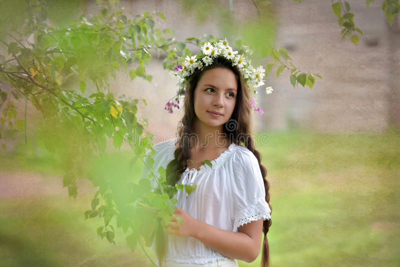 Girl with braids and a wreath of daisies royalty free stock image