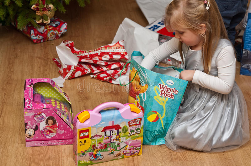 Girl with branded toys under Christmas tree. A young girl opens her birthday presents. Brands of Disney, Lego visible stock image