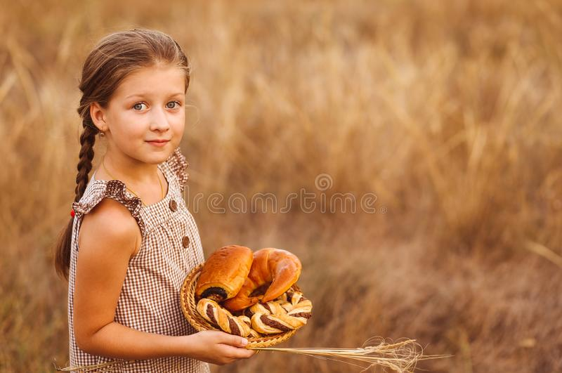 Girl with bread and buns in basket. Child is holding a lot of loaves in hands in the field stock images