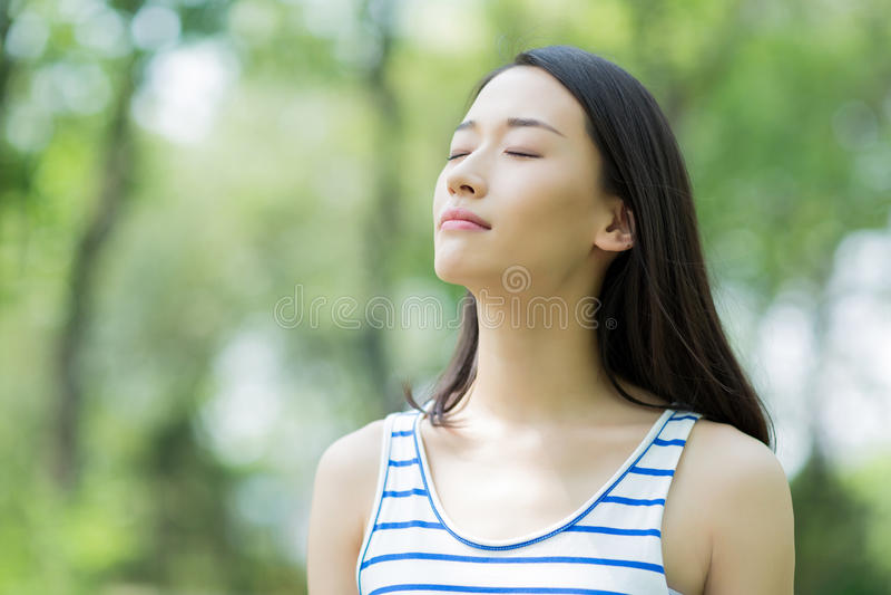 Girl breathing. Asian girl outdoor breathe fresh air in the prak royalty free stock photo