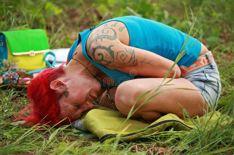 Girl breathing pranayama. A young girl woman with red hair and tattoos liying bending over the carimate and meditating in trance standing in asana doing yoga stock image