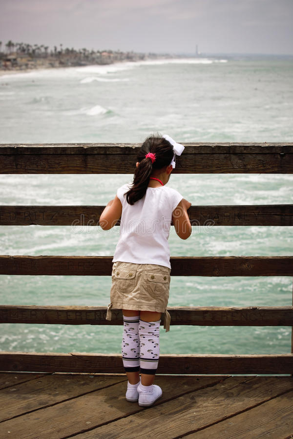 Girl on bridge. Little girl standing on a bridge watching the ocean stock photo