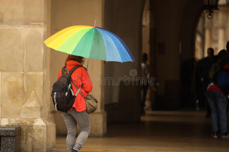 A girl in bright autumn clothes with a large umbrella of all colors of the rainbow walks in the city in the rain. Gay parade of royalty free stock photo