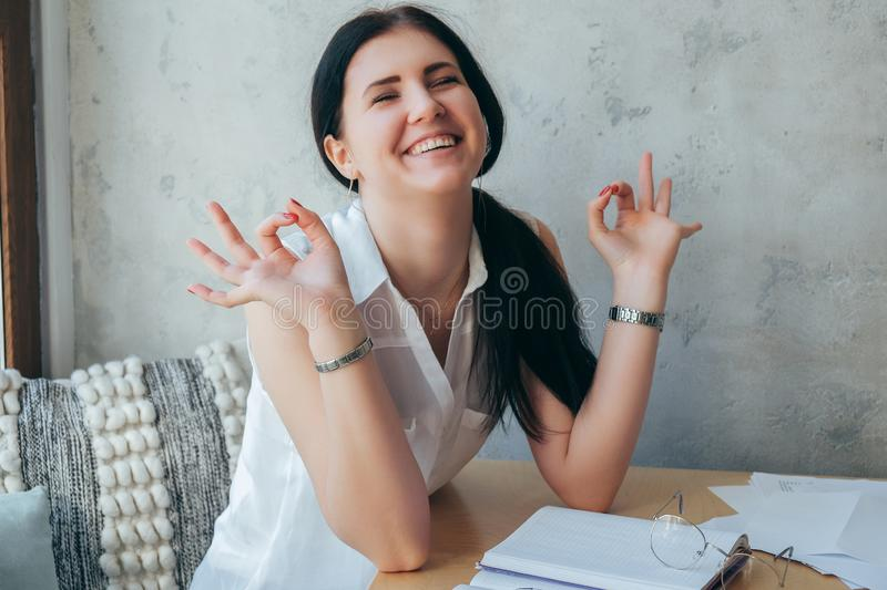 A girl in bright clothes sits on a gray background, smiles and holds her hands in a rest pose. Relaxation and rest at work royalty free stock photos