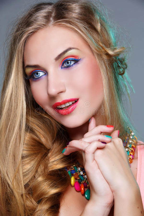 Girl with bright colorful makeup. Closeup portrait of beautiful young woman with bright colorful makeup and matching neclace. Emotions. Over grey background stock image