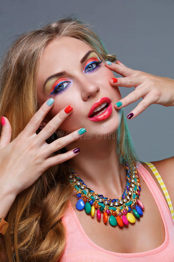 Girl with bright colorful makeup. Closeup portrait of beautiful young woman with bright colorful makeup and matching neclace. Emotions. Over grey background stock photography