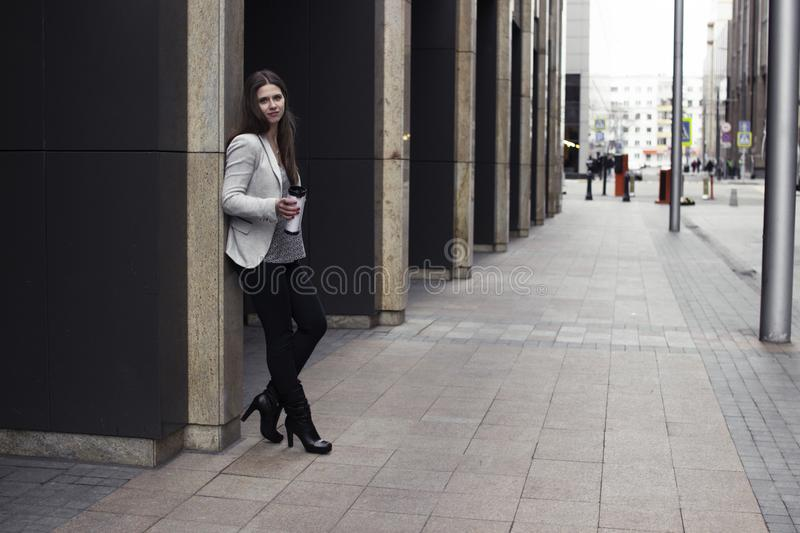 A girl in a bright jacket stands near the wall stock photography