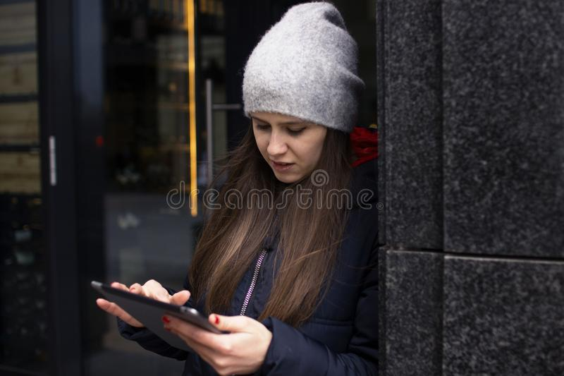 A girl in a bright jacket stands near the wall stock photos