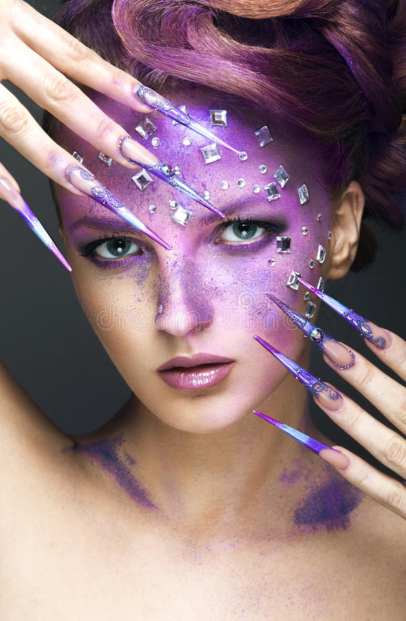 Girl with bright purple creative makeup with crystals and long nails. Beauty face. Picture taken in the studio on a gray background stock images