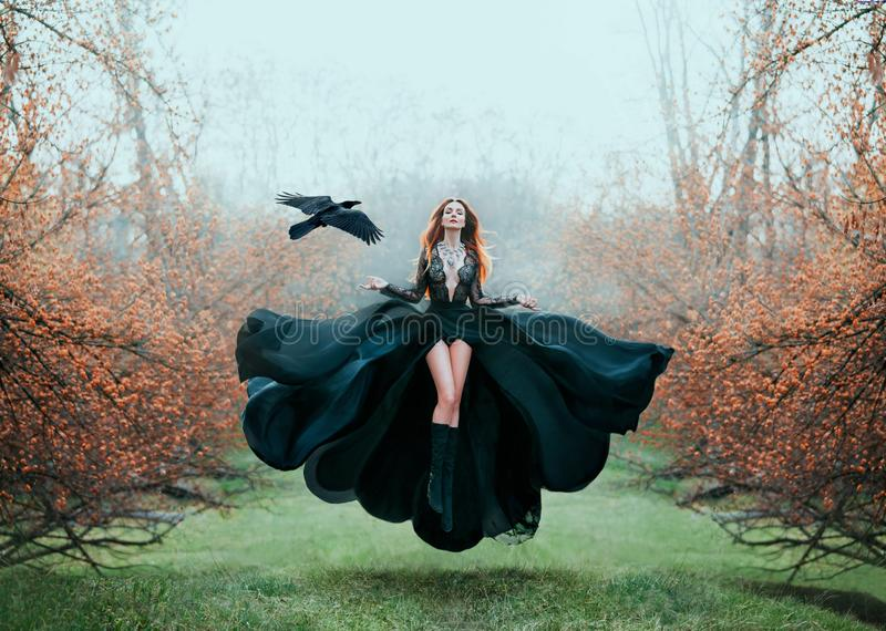 Girl with bright red hair levitates above ground, powerful sorceress, forest goddess in black flying dress with lace on stock image