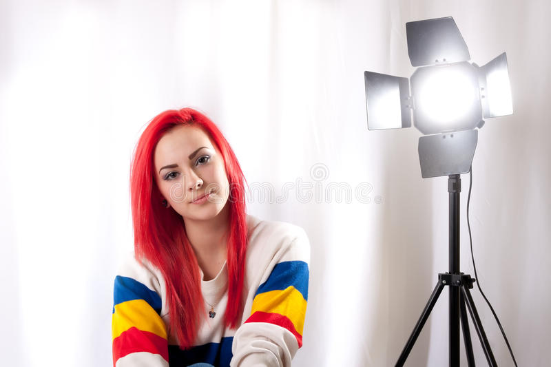 Girl with bright red hair with a studio flash stock image