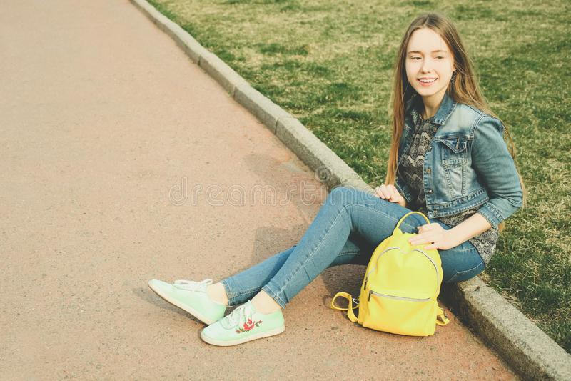 Girl with  bright stylish yellow backpack stock photos