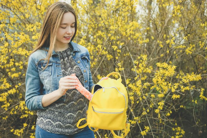 Girl with  bright stylish yellow backpack stock photo