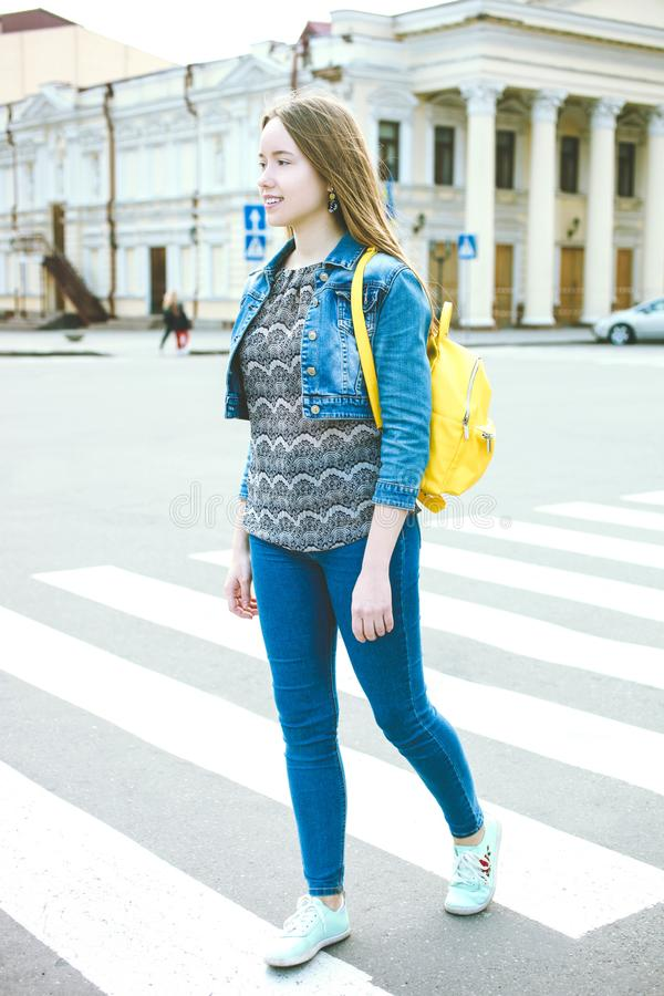 Girl with  bright stylish yellow backpack royalty free stock images