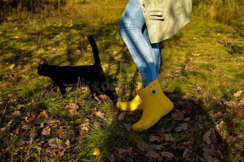 A girl in bright yellow boots walks with her beloved black cat royalty free stock images