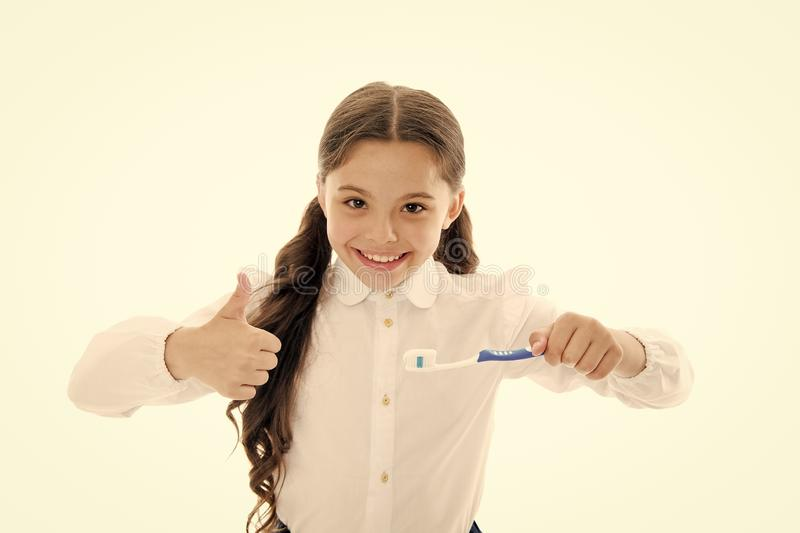 Girl brilliant perfect smile holds toothbrush with drop of paste white background. Child holds toothbrush and shows stock photography