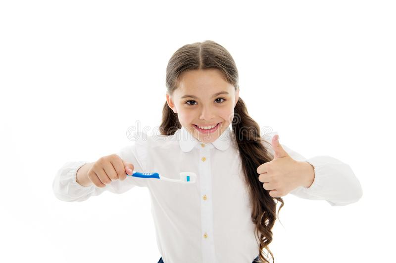 Girl brilliant perfect smile holds toothbrush with drop of paste white background. Child holds toothbrush and shows stock images