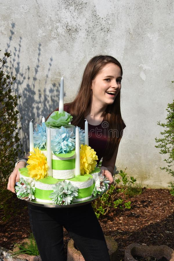Girl brings birthday cake made of toilet paper. Cute teenage girl brings a gift, a birthday cake made of toilet paper rolls decorated with flowers of paper stock photography