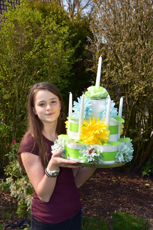 Girl brings birthday cake made of toilet paper. Cute teenage girl brings a gift, a birthday cake made of toilet paper rolls decorated with flowers of paper stock images