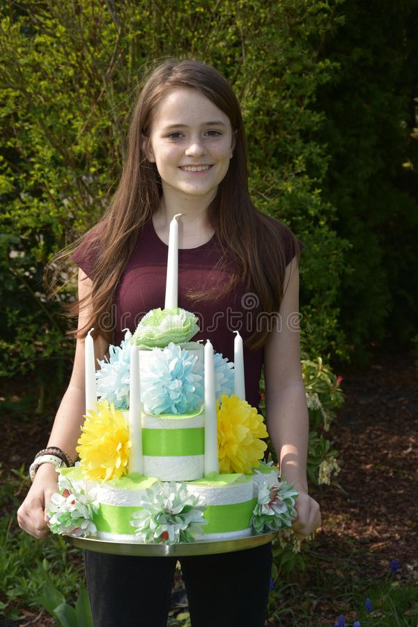 Girl brings birthday cake made of toilet paper. Cute teenage girl brings a gift, a birthday cake made of toilet paper rolls decorated with flowers of paper royalty free stock image