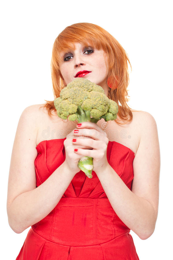 Girl with broccoli in red dress isolated stock image