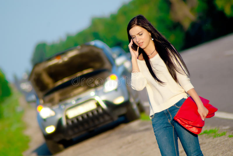 Girl with a broken car royalty free stock image