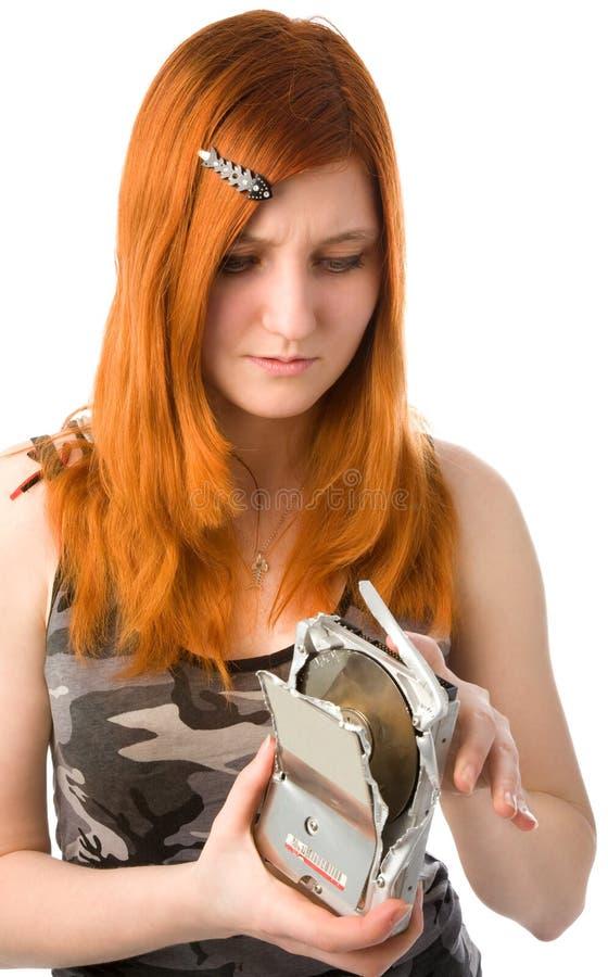 Girl with broken hard drive. Redhead girk looking to the broken hard drive stock image