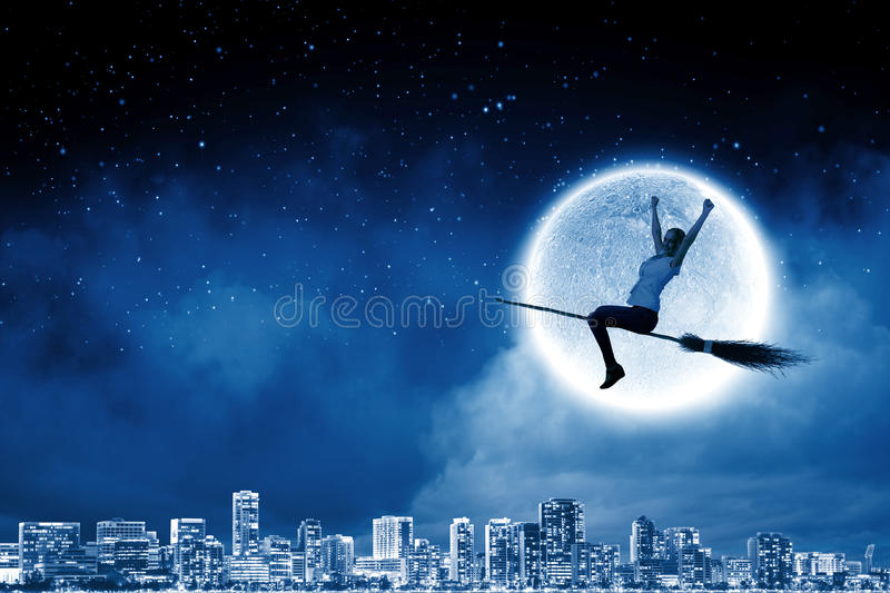 Girl on broom. Young girl in casual flying on broom high in sky stock photography
