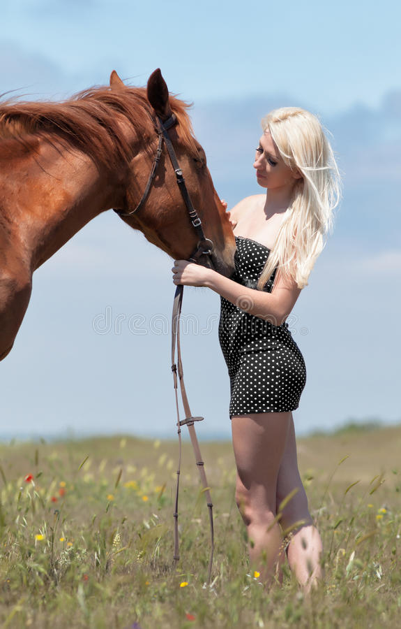 Girl with brown horse. Blonde woman stroking gelding. Young blonde woman in polka-dot dress with brown horse royalty free stock photos