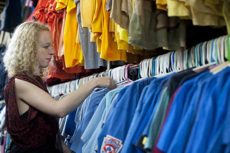 Girl browsing thrift clothing. Girl browsing through used t-shirts in a thrift store stock photos