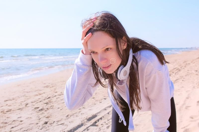 Girl stop jogging to catch breath sport run training sea sand beach headphones. Girl brunette have a break on running training at sea sand beach. She stops royalty free stock photography