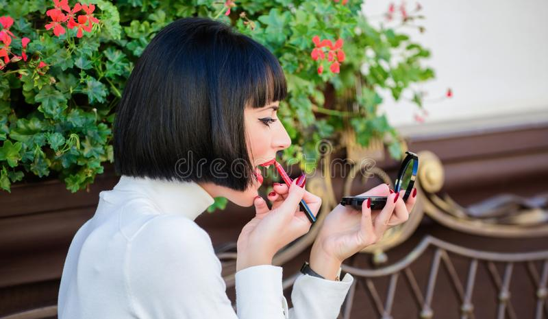 Girl brunette with lipstick looking in mirror check her makeup appearance. Girlish secrets concept. Woman making makeup stock photo