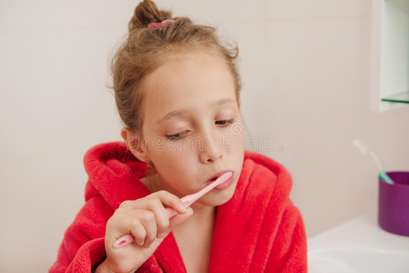 The girl brushes teeth in a bathroom in a red dressing gown stock photo