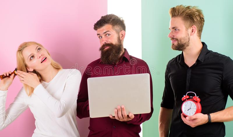 Girl brushing hair while men work with laptop. Discipline and timing. Some people are always running late. Why women. Always late. Woman need more time to do royalty free stock photos