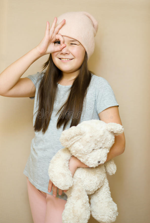 Girl is brushing her teddy bear stock images